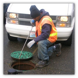 Staff setting rat bait in Seattle sewer system