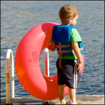 Boy with life jacket and inner tube