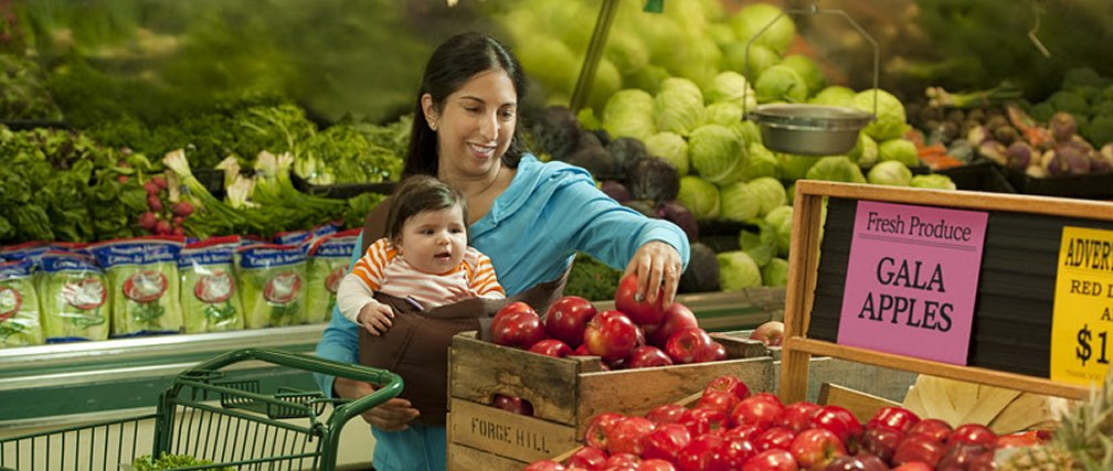 Mother with infant shopping for produce