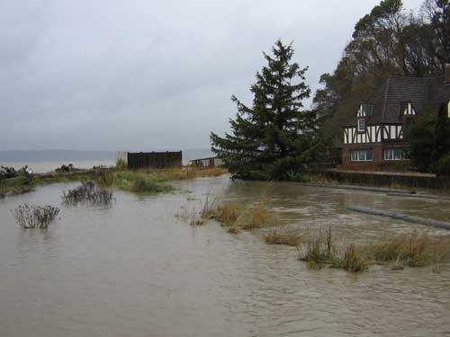 Photo of flood waters completely overflowing creek banks, with Puget Sound and house in the background
