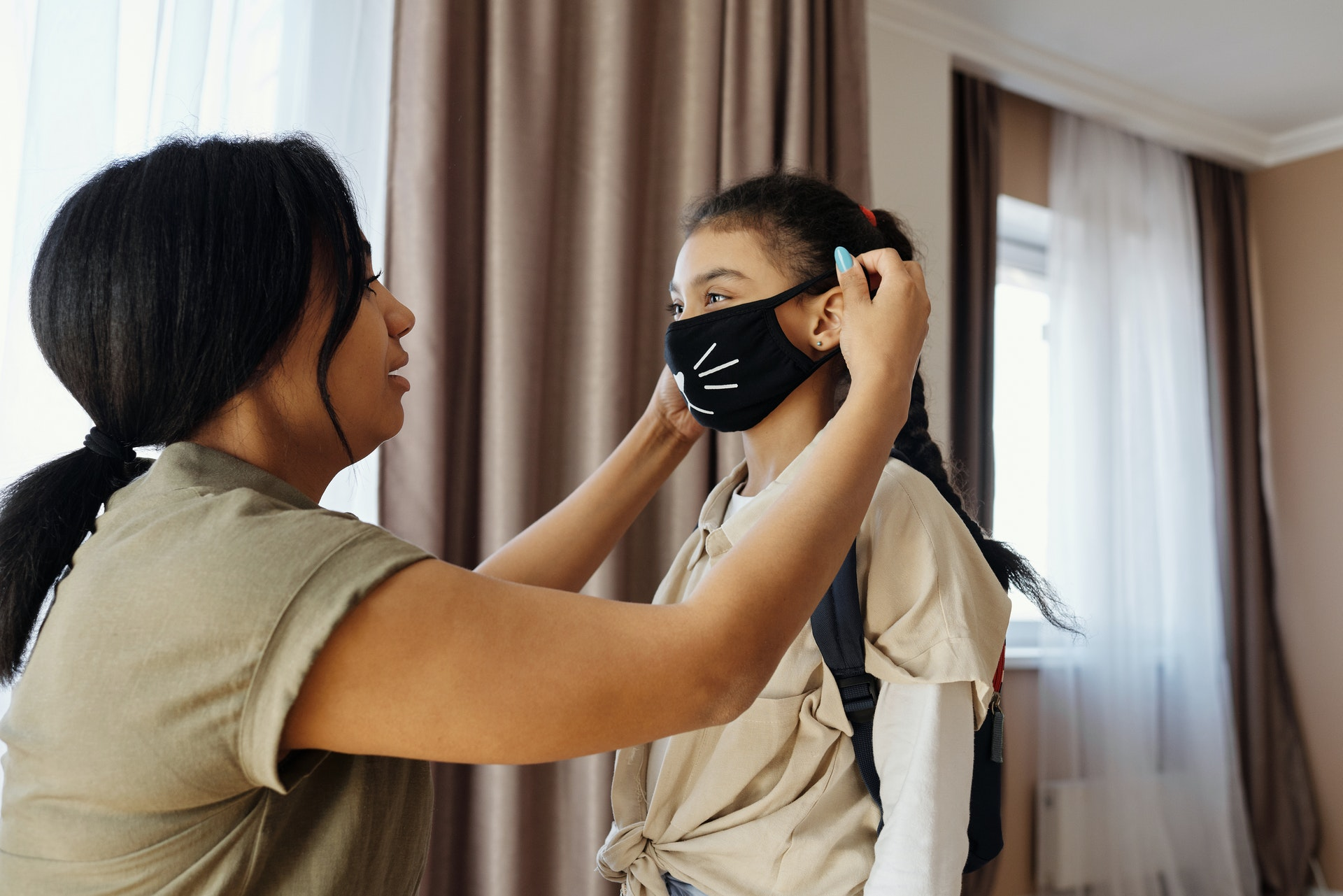 Mother putting a facemask on her child