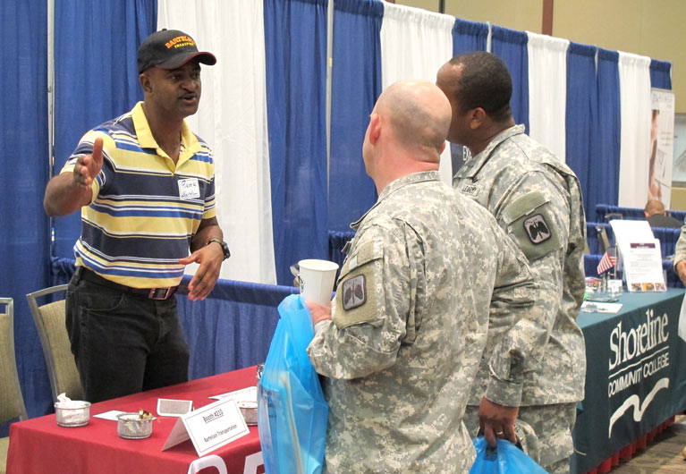 Two service members in uniform talk with a man at a public event.