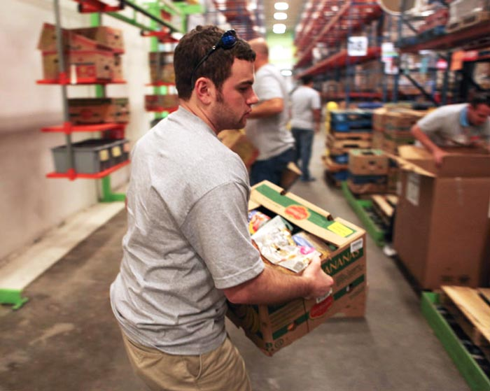 Warehouse worker moving boxes of food in a commercial food bank