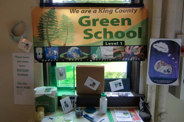 "Information table at Kings School showcasing products made from recyclable materials and the school's ""We are a Green School"" banner"