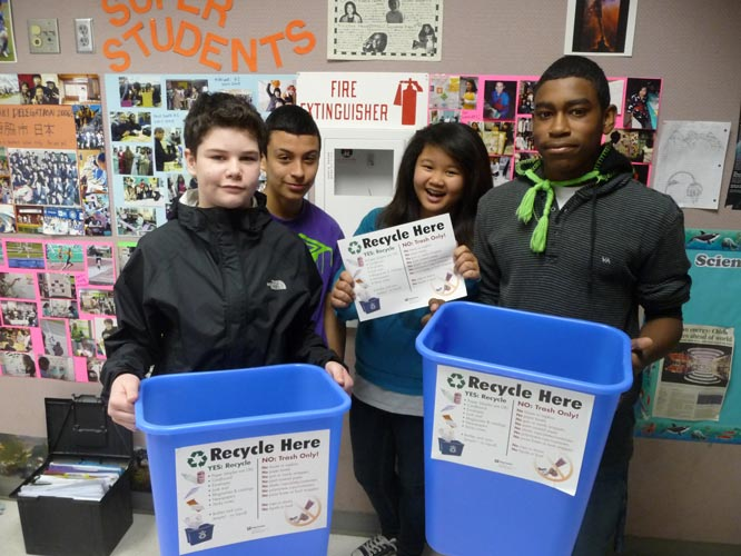 Students at McKnight Middle School attach signs to recycling bins