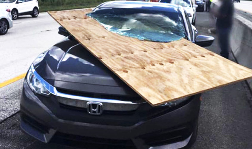 image: sheet of plywood sliced through a car windshield - Secure your load today and every day!