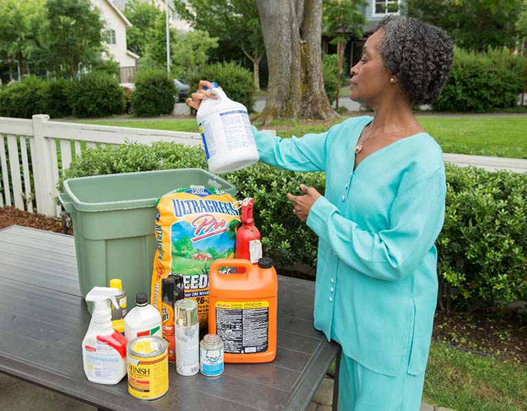 An older woman dressed in a light blue pantsuit is standing outside looking at common household hazardous products that are placed on a table in front of her.
