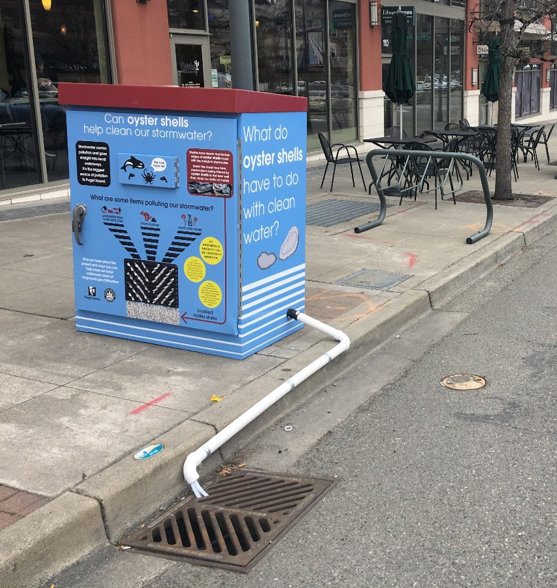 Sampling equipment at a retrofitted catch basin in Mercer Island Town Center with interpretive signage