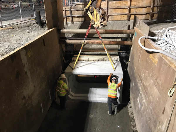 A square concrete pipe (box culvert) is lowered into a trench box and crew members set it in place.
