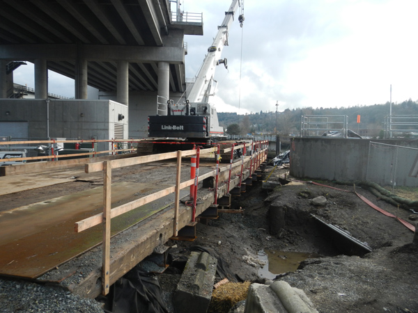 A wooden platform is shown underneath the First Avenue South Bridge. A crane sits on top of the wooden platform.