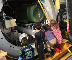 Kids looking at a tunnel boring machine