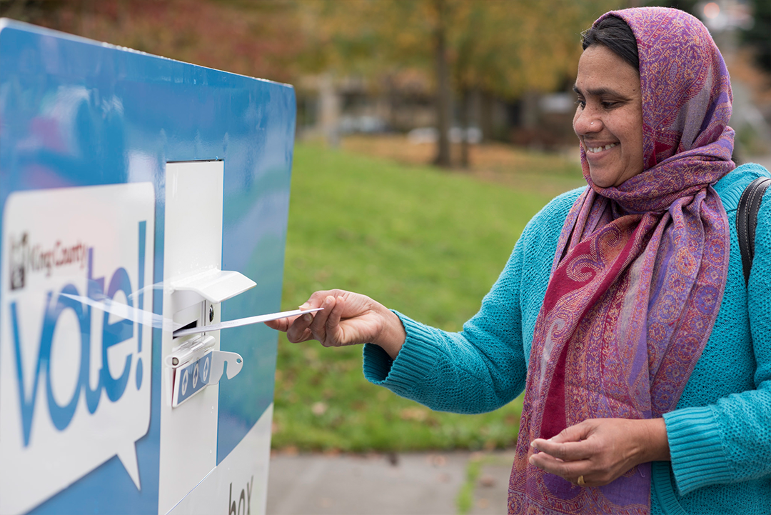 Voter returning ballot at drop box