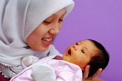 Young mother in a hijab holds her infant daughter.
