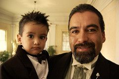 Father in a tuxedo, holds his small son wearing a tuxedo.