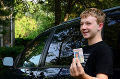 Young looking teen holds up his driver's license.