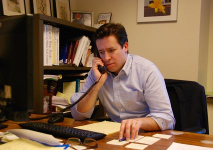 Val Richey sits at his desk and listens on the phone.