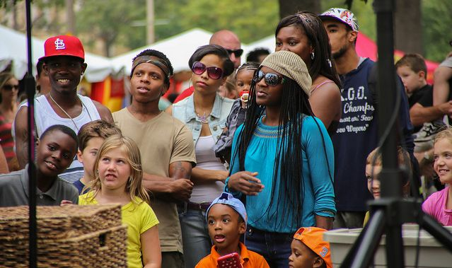 A group of people in the audience look on at a street carnival.