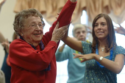 A smiling elderly woman gets a little help raising her arm from a younger woman.