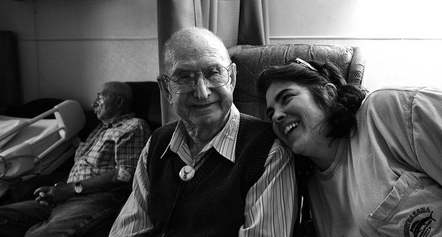Elderly man poses with a laughing young woman in a nursing facility.