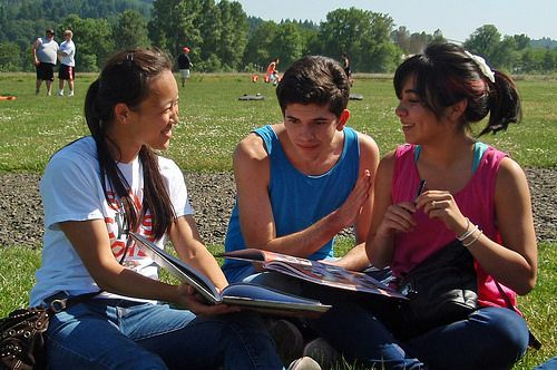 Three teens sit on a lawn looking at their yearbooks.