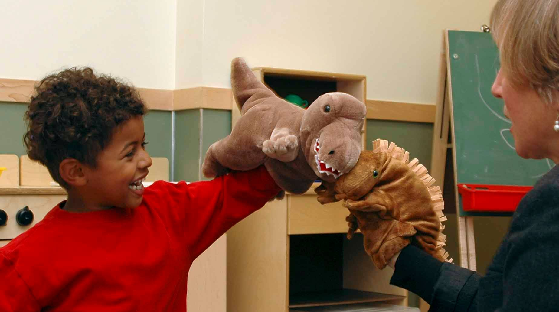 A child and teacher playing with stuffed animals