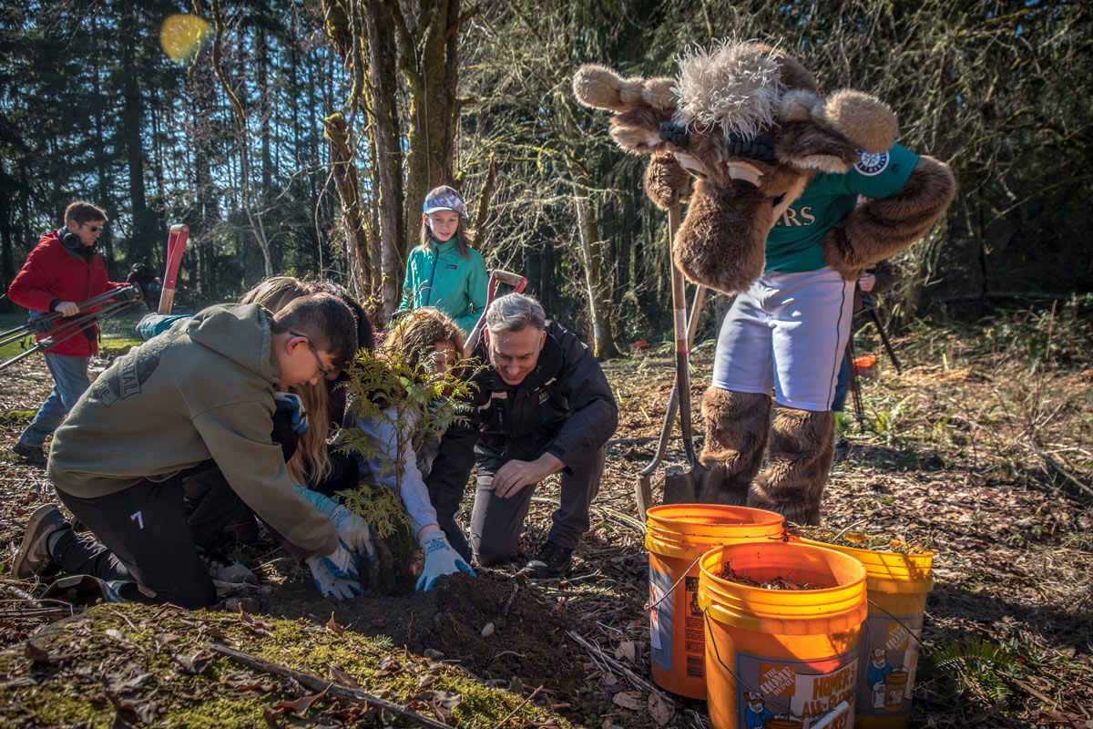 Executive Constantine and local students are joined by Mariner Moose at a ceremonial tree planting at King County's Big Finn Hill Park near Kirkland.