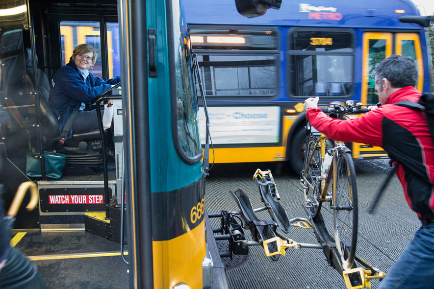 A man loads a bike onto a Metro bus.