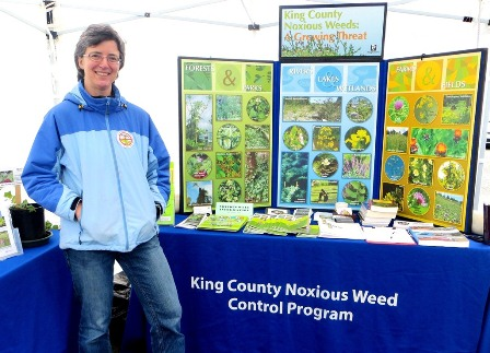 Education Specialist Sasha Shaw with King County Noxious Weed Program information booth - click for larger image
