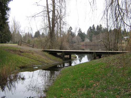 Photo of stream flowing out of a lake underneath a footbridge