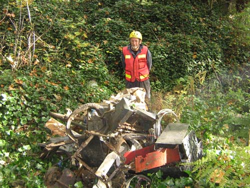 Photo of man standing behind pile of trash collected in ravine beneath Sylvester Bridge