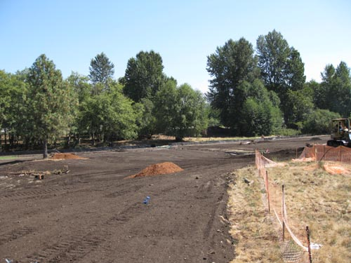 Photo of freshly graded dirt in field with trees in background