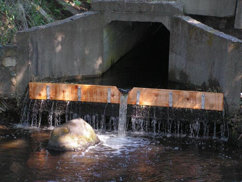 Photograph of culvert with wooden board installed at lip of culvert