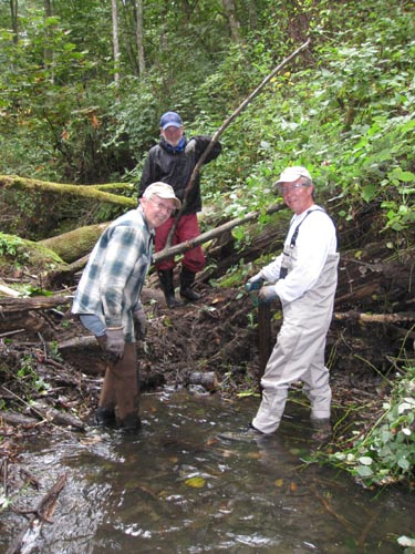 Photo of three men standing in a stream in front of a log jam
