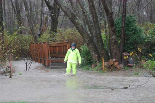 Photo of man in rain gear walking through ankle deep water with footbridge in background