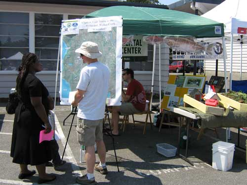 Photo of people looking at map on easel at booth at 2008 Strawberry Festival