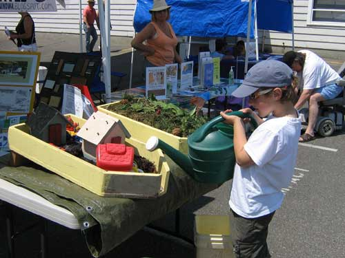 Photo of boy using watering can to pour water on models of watersheds at 2008 Strawberry Festival