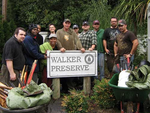 Photo of people standing next to a sign reading 'Walker Preserve.'