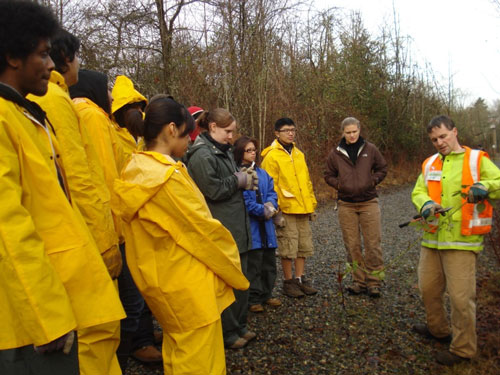 Photo of people in yellow rain gear watching a demonstration of how to identify weeds