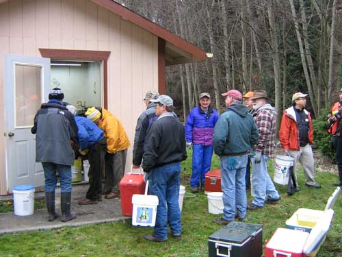 Photo of people with ice chests and buckets lined up outside small building