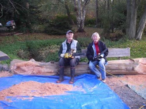 Photo of man and woman holding chain saws and sitting on bench that has salmon head and tail carved onto the ends of the bench.
