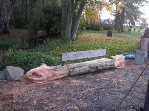 Photo of bench at Normandy Park Community Club with carving of head and tail of salmon at either end of bench.