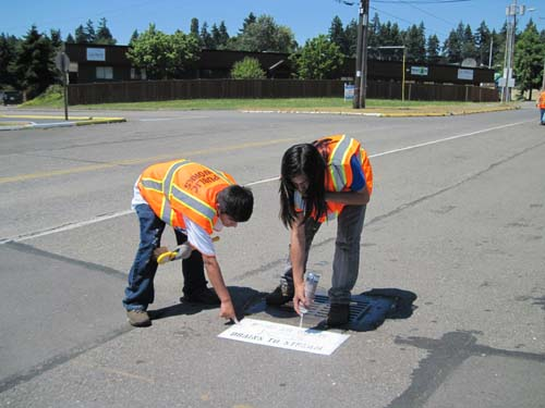 Photo of two teenagers in safety vests spray painting a stencil on pavement next to a storm drain