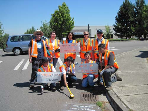 Photo of nine people in safety vests holding plastic stencils and spray paint next to a storm drain