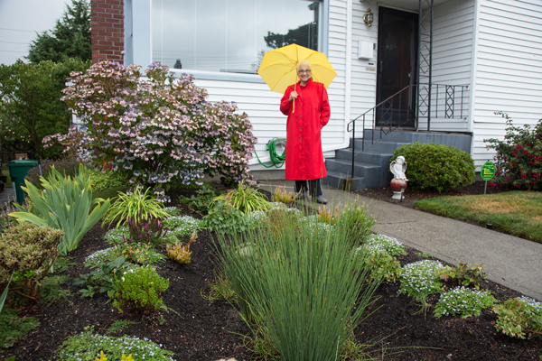 woman in red coat with yellow umbrella next to rain wise garden