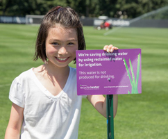 girl next to recycled water sign